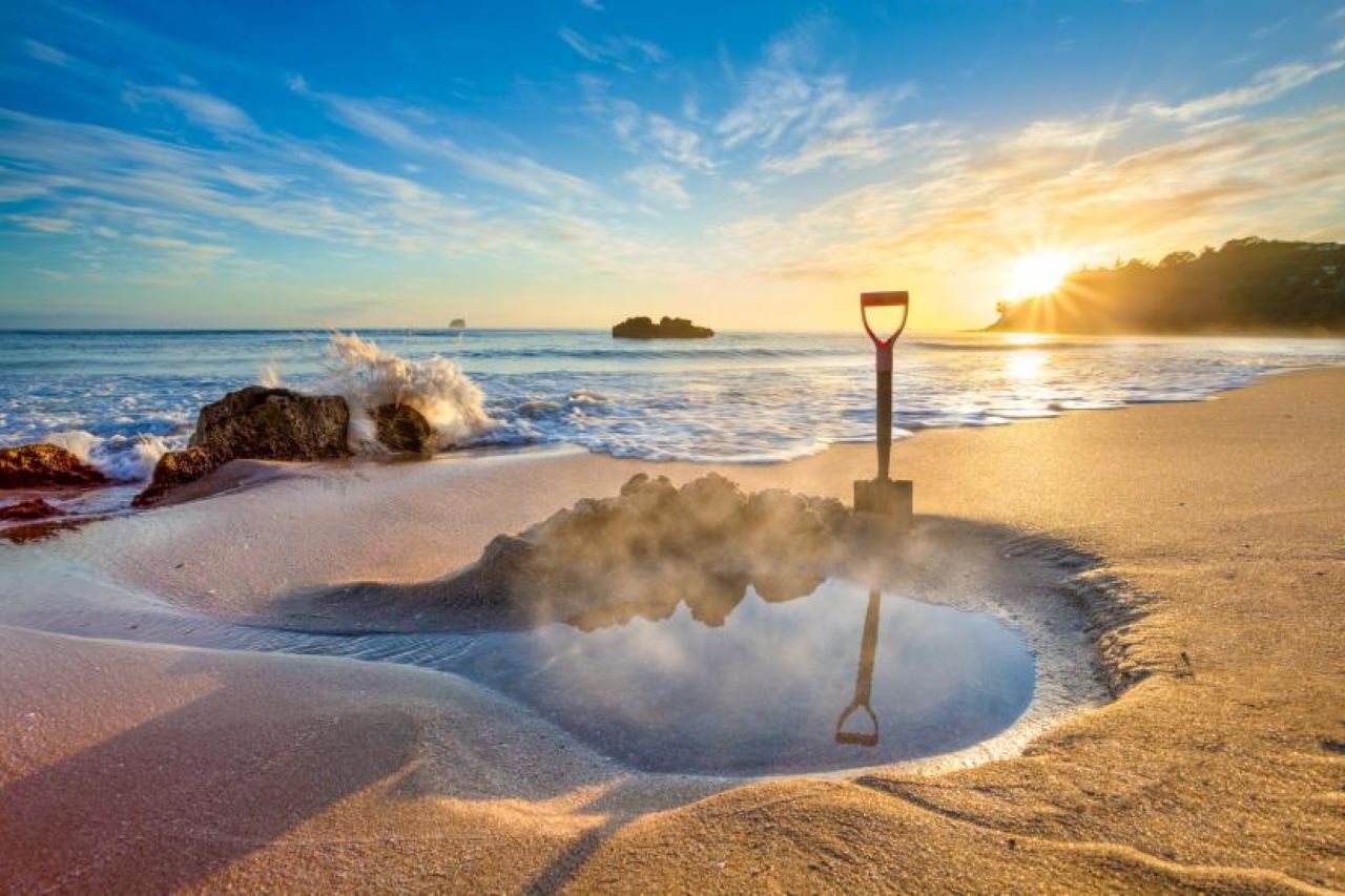 A small pool with steaming water on a beach with the sea and clear sky in the background