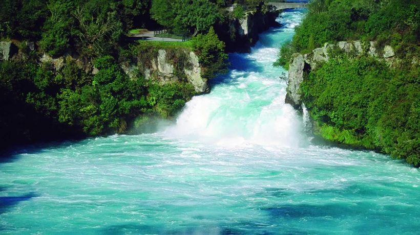 Blue water of the Huka Falls at Lake Taupo between green river banks