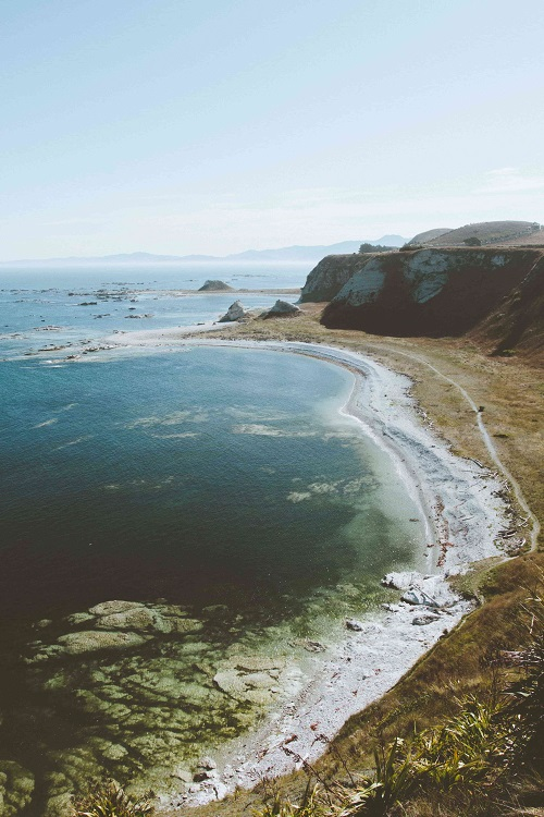 View of a long beach beside a cliff with a clear horizon at Kaikoura, New Zealand