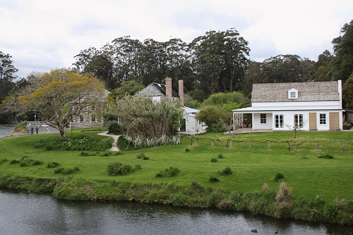 Two old buildings beside a river surrounded by gardens