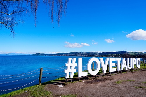 Sign saying Love Taupo in front of a blue lake at Lake Taupo, New Zealand