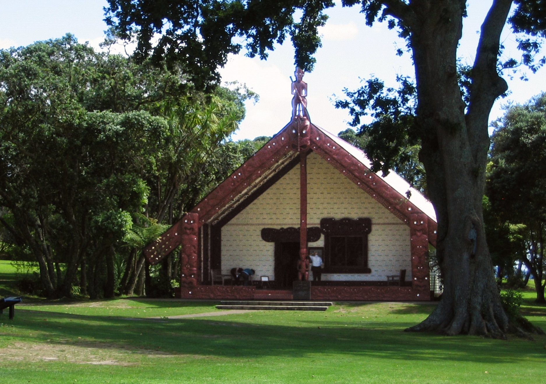 Building with a carved pillar under a tree, Waitangi Treaty Grounds, New Zealand