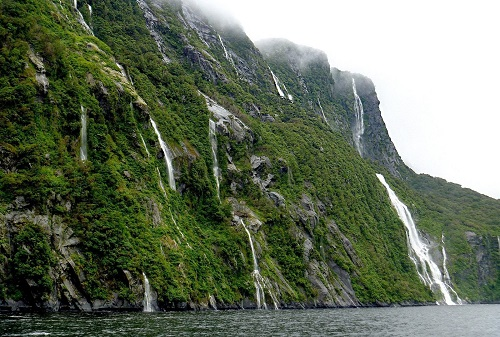 Waterfalls cascading down a green mountain into water