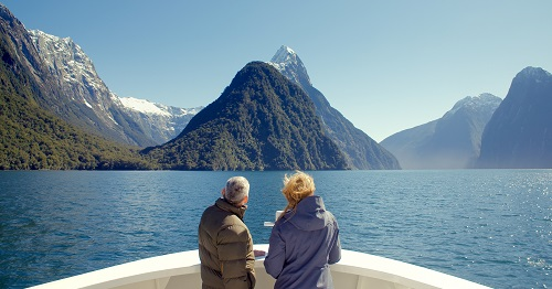 A man and woman looking out over a lake with mountains in the background at Milford Sound