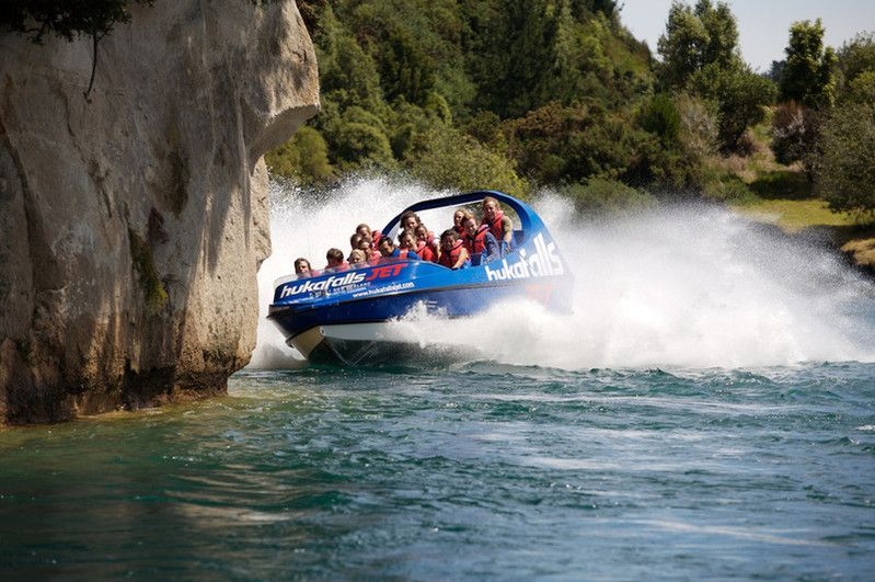 Passengers on a motorboat in the water beside a cliff at Huka Falls at Lake Taupo