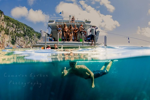 Diver under water with people on a boat above water in the background
