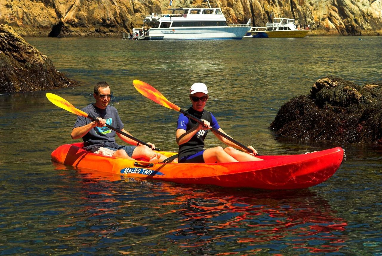 Two rowers in a sea kayak at Poor Knights Marine Reserve, New Zealand