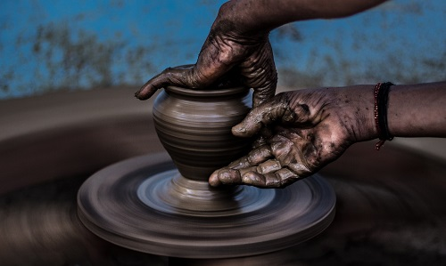 The hand of a potter forming a vase on a pottery wheel