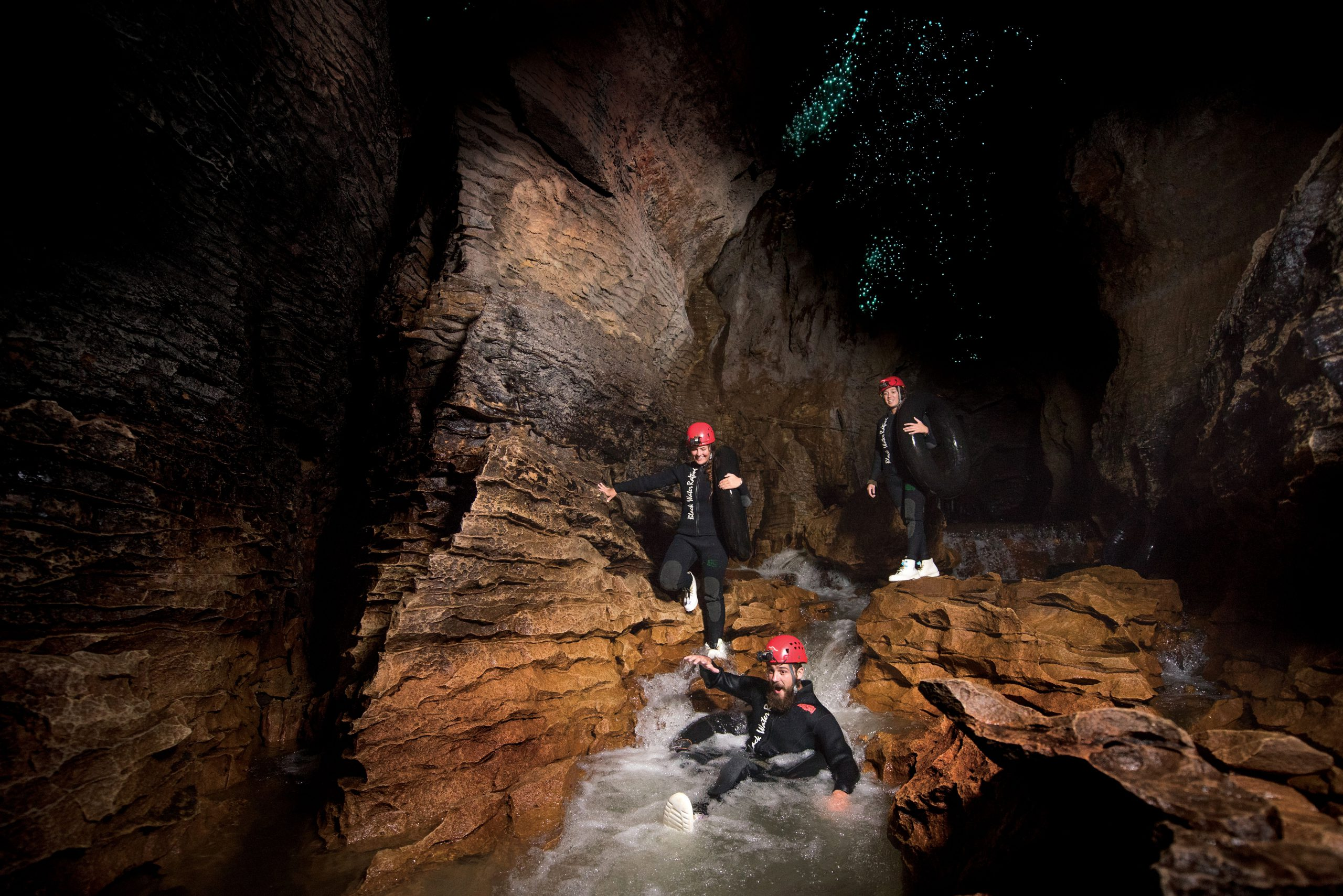 Black Water Rafters sliding down underground waterfalls at Waitomo Caves